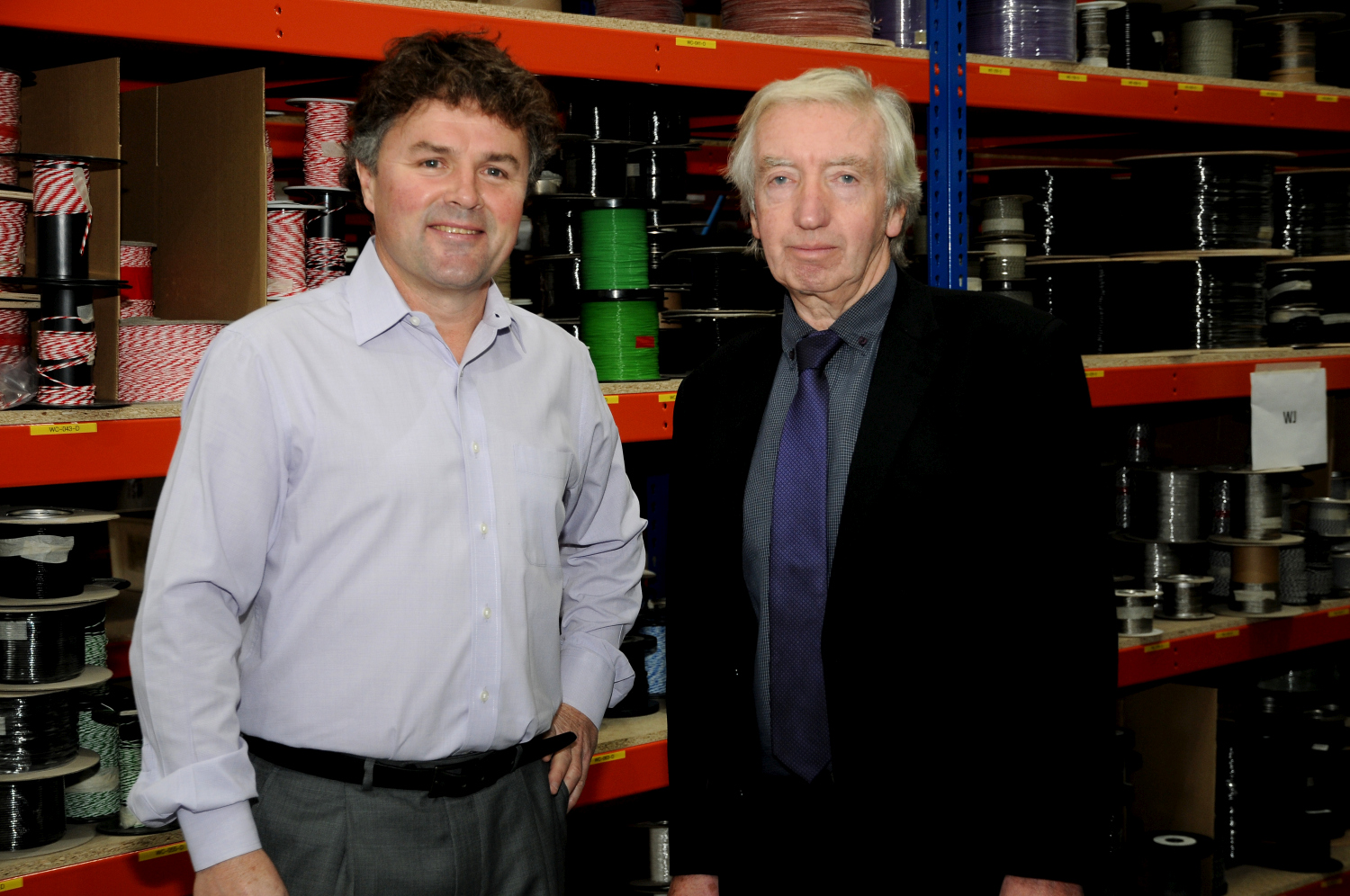 Two men in an industrial unit. Grey haired man to the far left is wearing a black suit, dark grey shirt and navy tie and the other man has dark hair, grey trousers and light blue shirt.