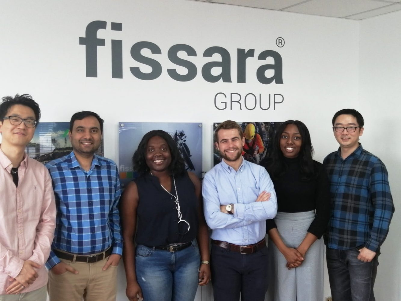 A group of employees stood in front of a Fissara group branded wall