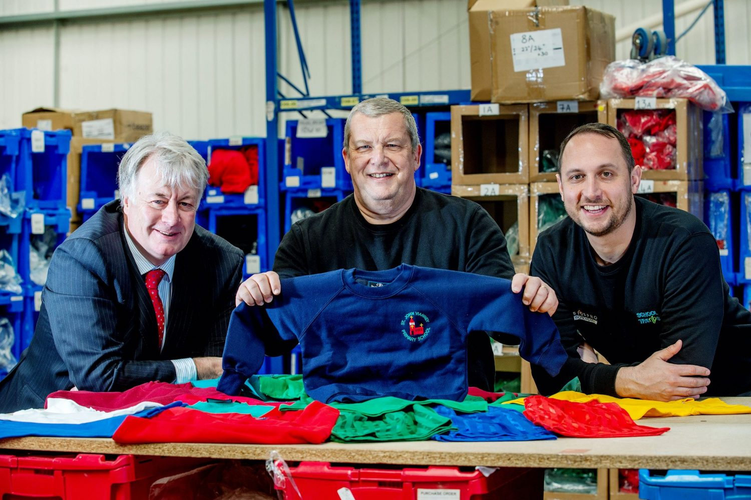Three men in a clothing factory, man in the middle holding up a blue sweat shirt with a red logo, bearded man to the right hand side wearing a blue sweat shirt and man at the left hand end wearing a blue suit with a red tie has grey hair.