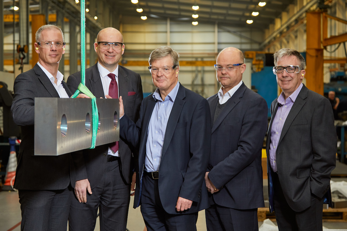 Five men inside a factory, they are all wearing protective glasses. Man to the far right is wearing a dark grey suit and a purple shirt and man to the far left has his hand on a rectangular piece of metal.