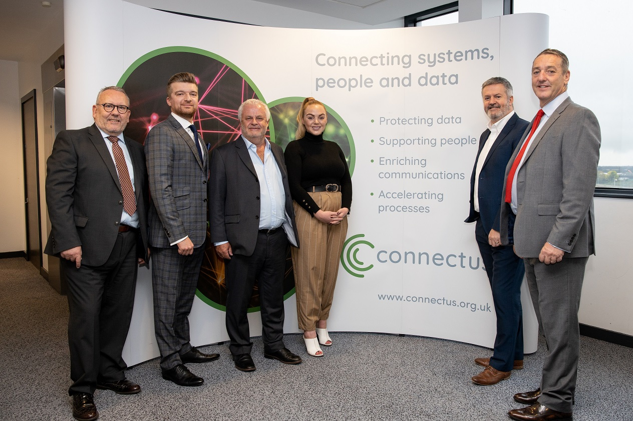 A group of employees from Connectus standing in front of a Connectus branded pop up banner