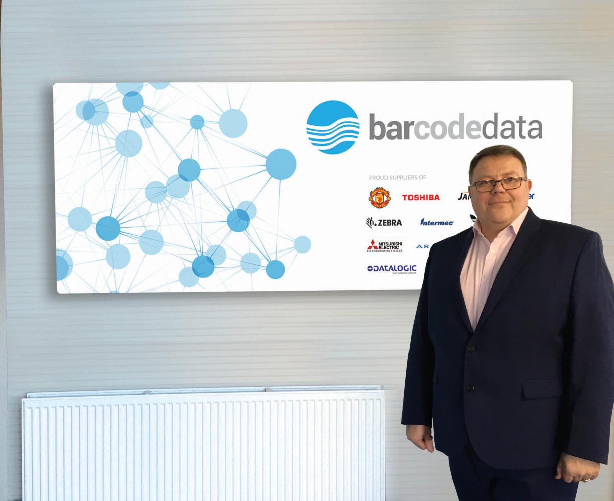 A man standing in front of Bar Code Data sign on a wall