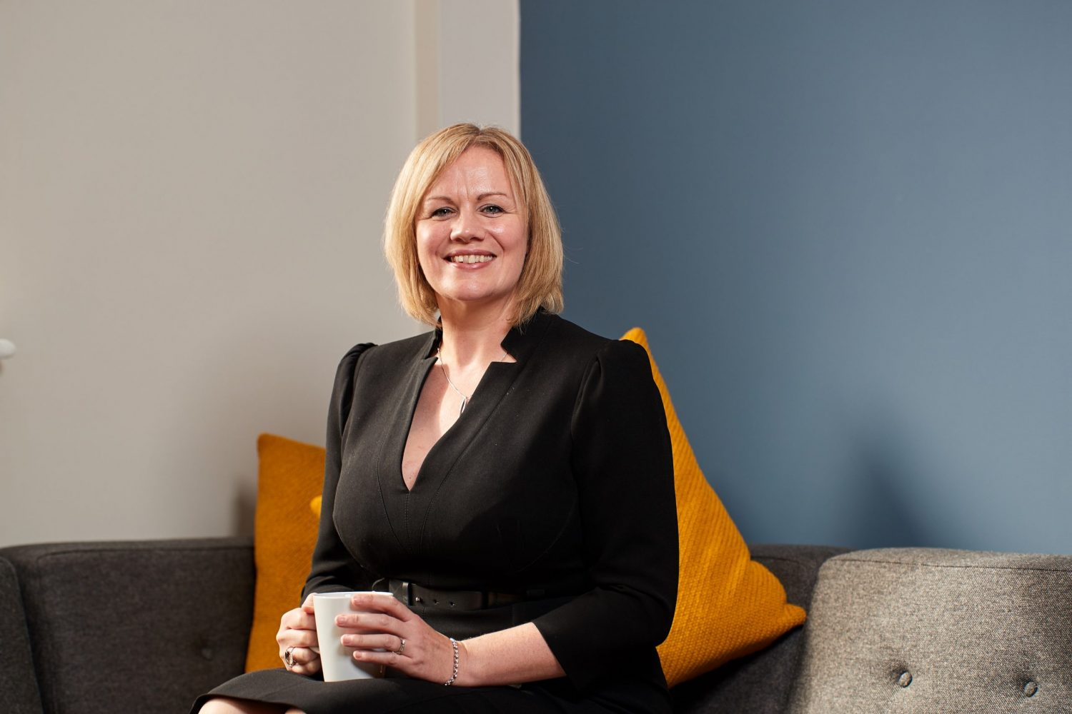 Joanne Whitfield, Fund Director at FW Capital sitting on a couch holding a mug