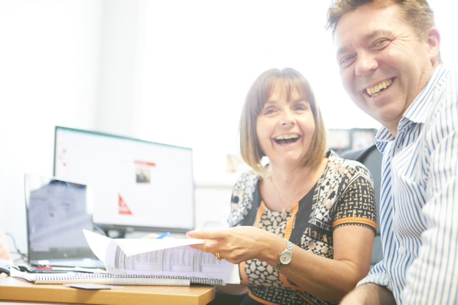 A man and a woman sat at an office desk laughing