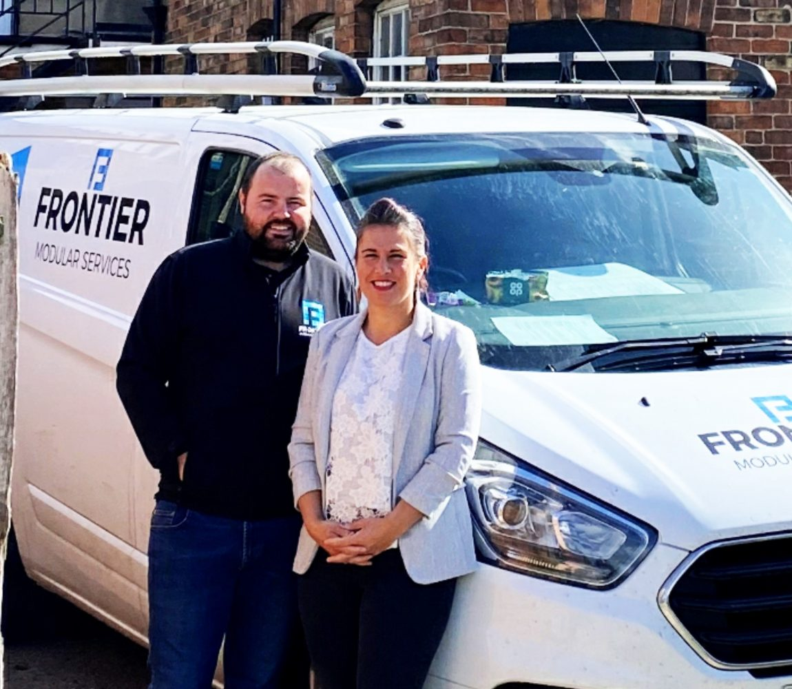A man and woman smiling and stood in front of a Frontier Modular Services van