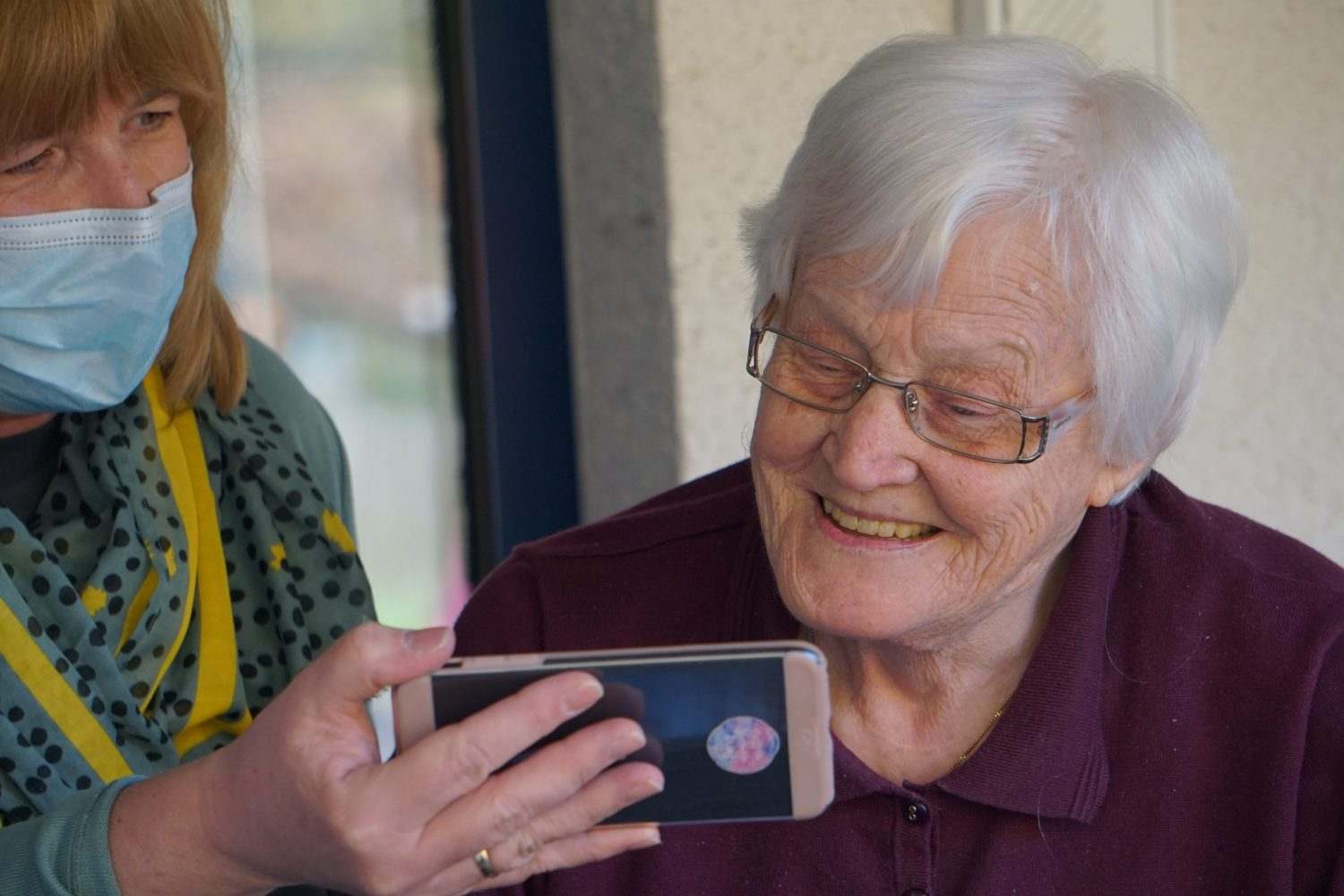 An elderly woman being shown something on a smartphone by a member of care staff wearing a face covering
