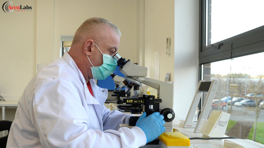 A man in a science lab wearing personal protective equipment looking into a microscope
