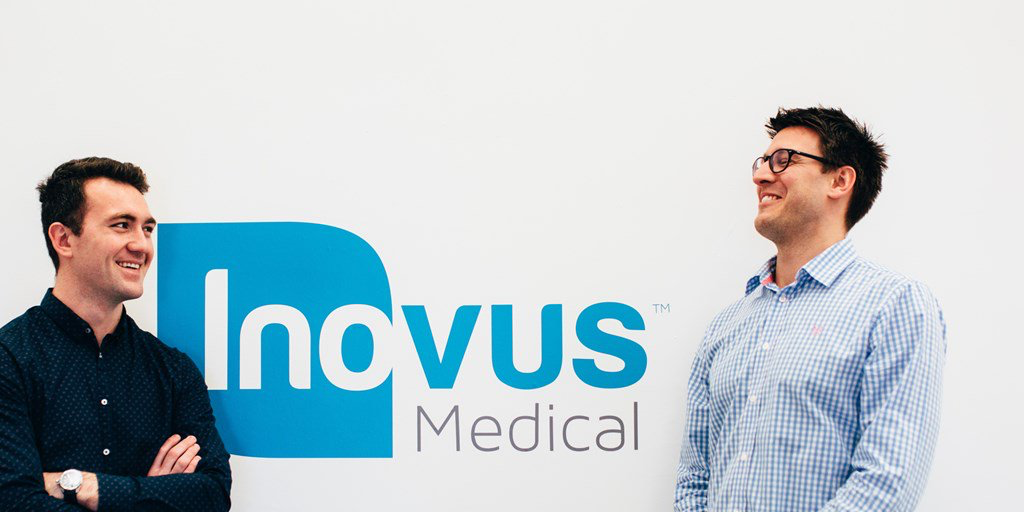 2 men from smiling and looking at each other in front of an Inovus Medical branded wall