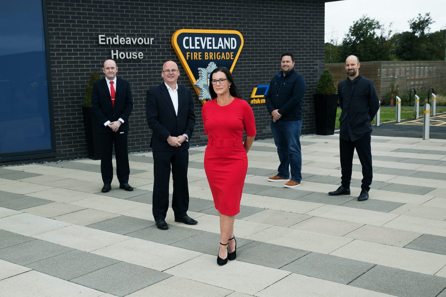 Business woman in a red dress standing in front of four business men. They are outside standing near a brick wall with signage for Cleveland Fire Brigade.
